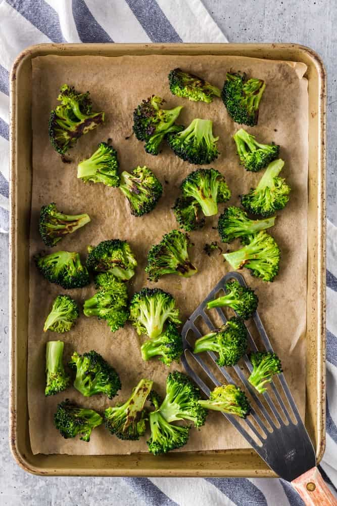 bright green roasted broccoli with charred edges on a parchment lined baking sheet after roasting in the oven