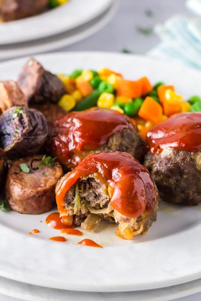 Onion Burger Mini Meatloaf covered in a bright red sauce on a white plate with a bite taken out of it