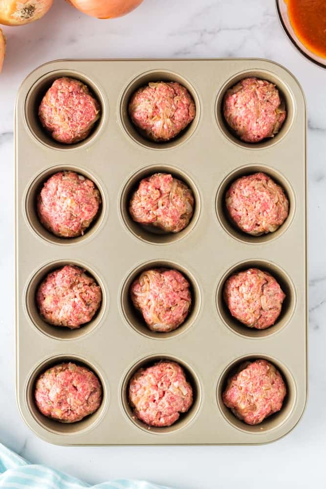muffin pan filled with twelve unbaked onion burger mini meatloaf