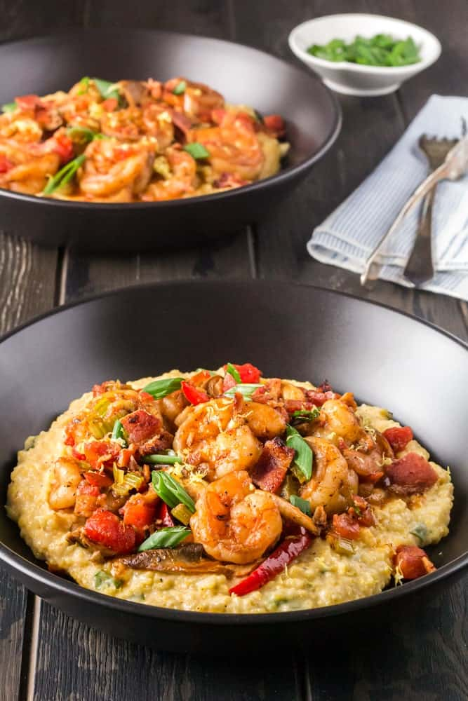 Black bowl filled with bright yellow grits, topped with shrimp smothered in a new orleans style buttery barbecue sauce and tossed with green onions, red bell peppers and mushrooms
