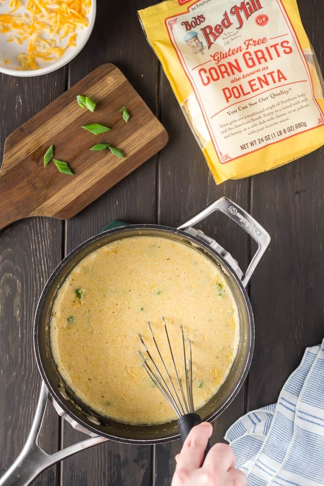 saucepan filled with bright yellow corn grits being whisked
