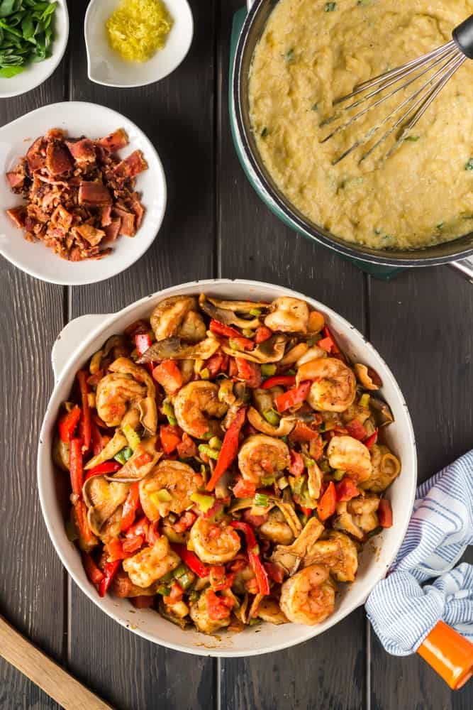 orange saute pan filled with cooked shimp, green onions, bell peppers and mushrooms with a bowl of bright yellow grits and small bowls filled with bacon, green onions and lemon zest on the side