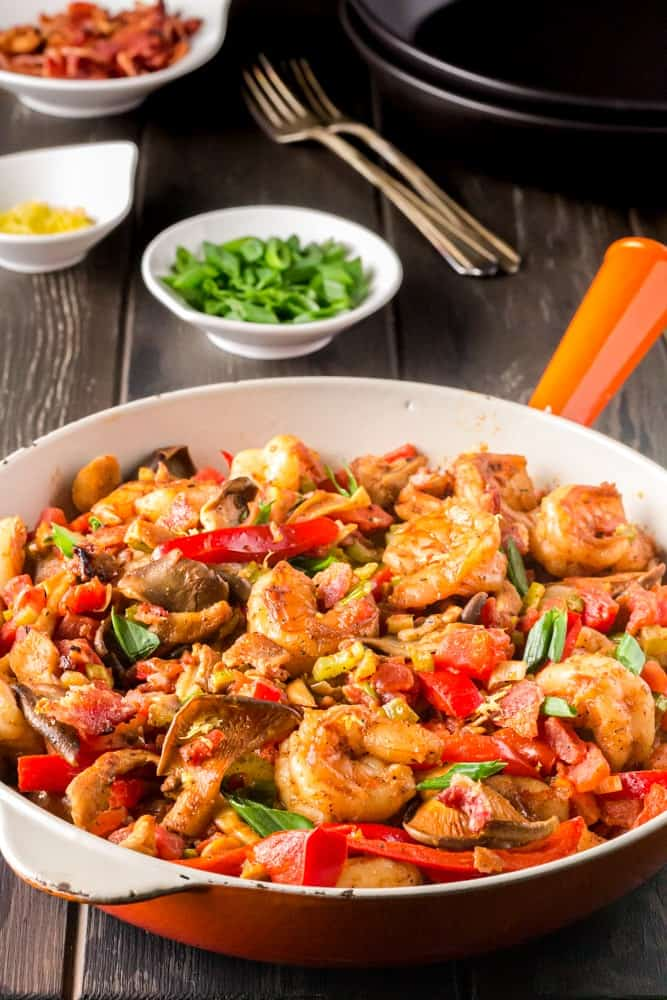Saute pan filled with bright yellow grits, topped with shrimp smothered in a new orleans style buttery barbecue sauce and tossed with green onions, red bell peppers and mushrooms