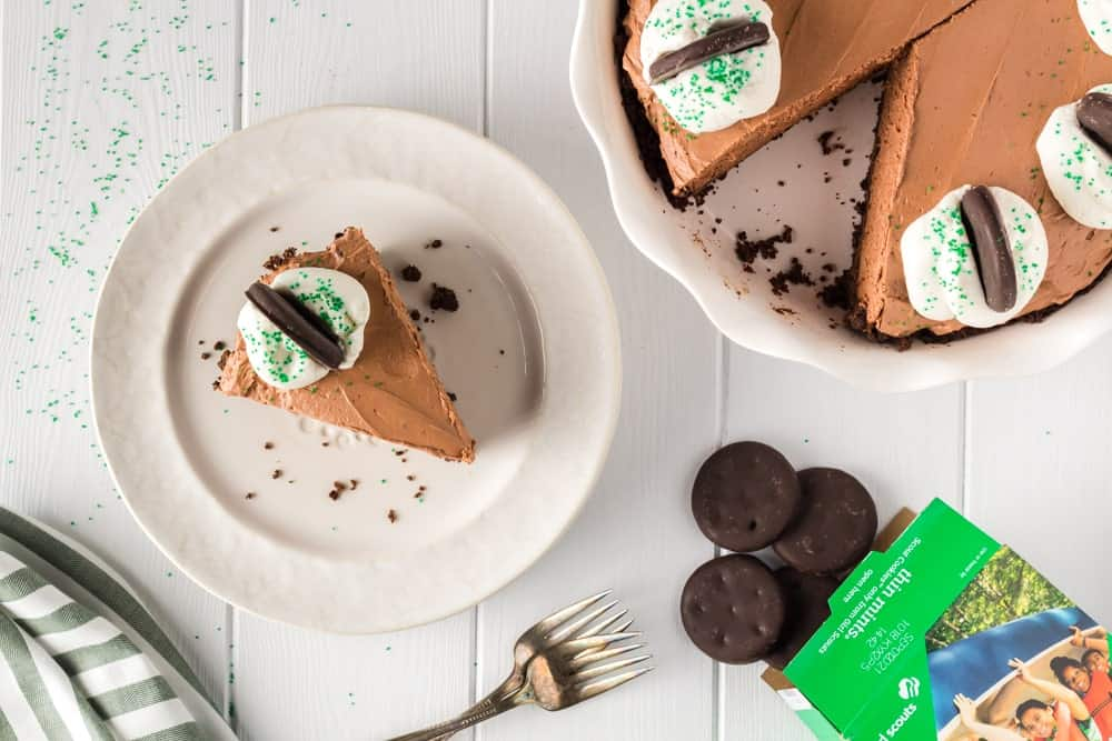 Single slice of brown thin mint chocolate cheesecake on a white plate with the whole cheesecake plate on the side missing a slice and thin mint cookies falling from the box