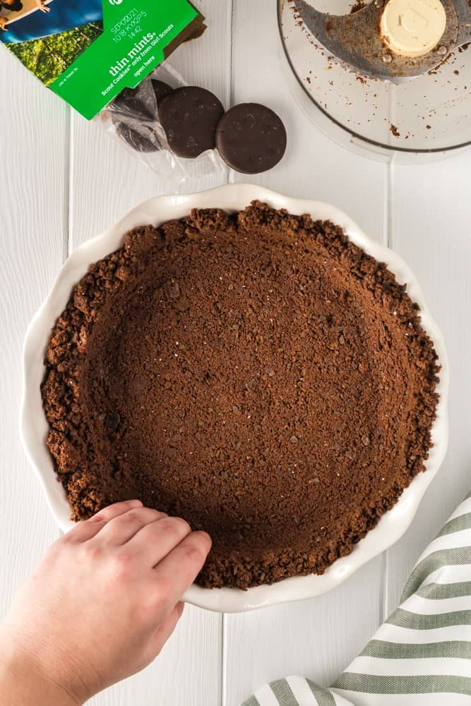 unbaked thin mint cookie crust being pressed by hand into a white pie plate
