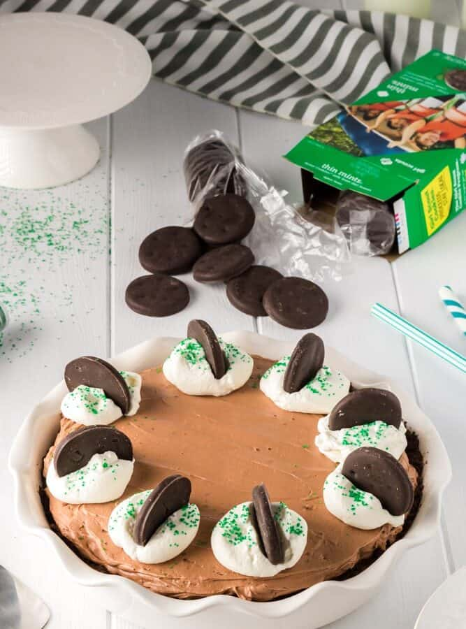 whole and unsliced brown thin mint no bake chocolate cheesecake with white dollops of whipped cream on each slice topped with bright green sprinkles and a thin mint cookies