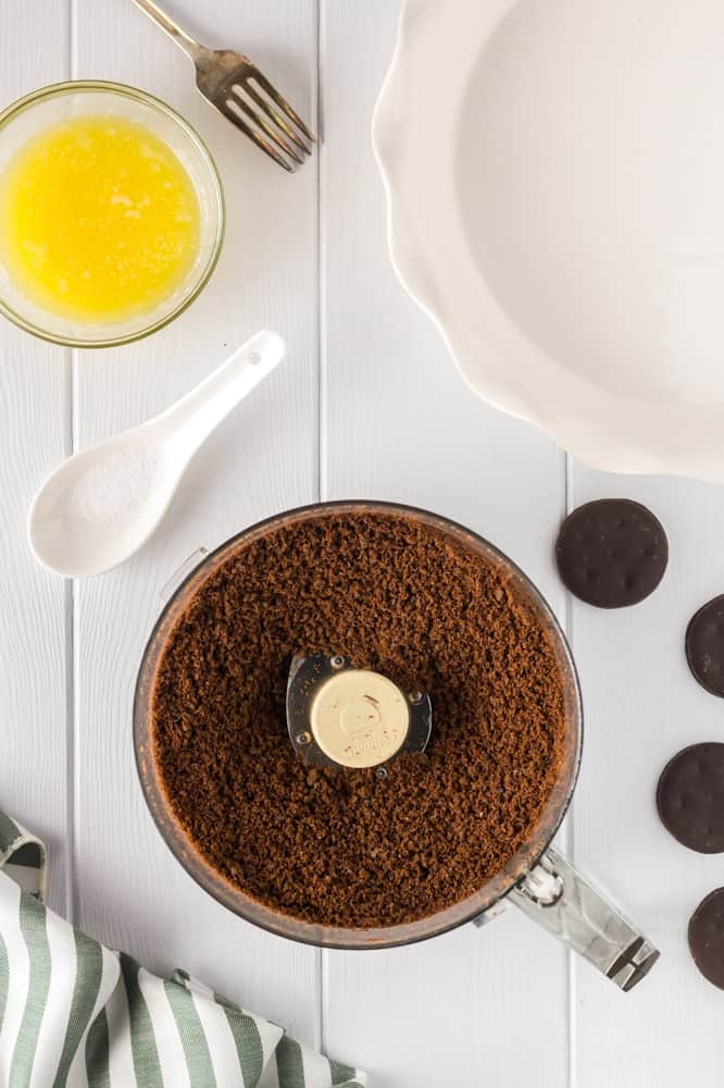 thin mint cookie crumbs in a food processor with a small bowl of melted butter and an empty white pie plate on the side
