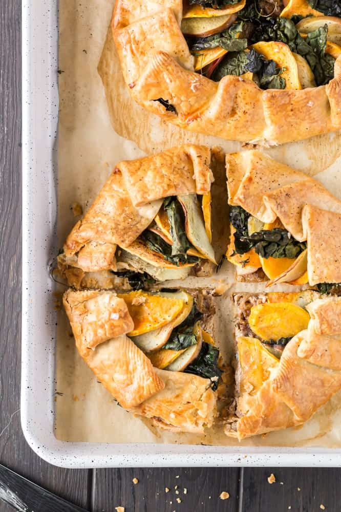golden brown round sweet potato, apple and kale galette filled with orange slices of sweet potato, green torn kale leaves and white apple slices on a white baking sheet lined with brown parchment paper