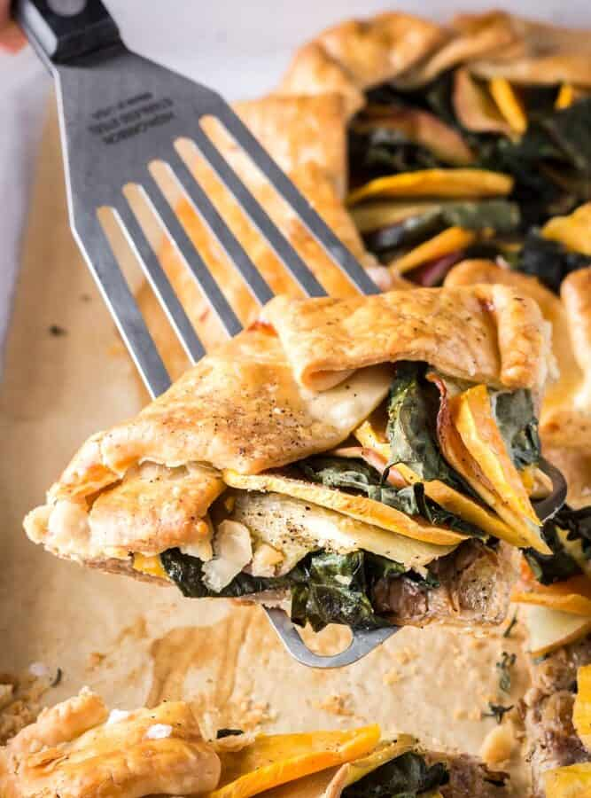 Slice of sweet potato, apple, and kale galette being picked up with a silver spatula