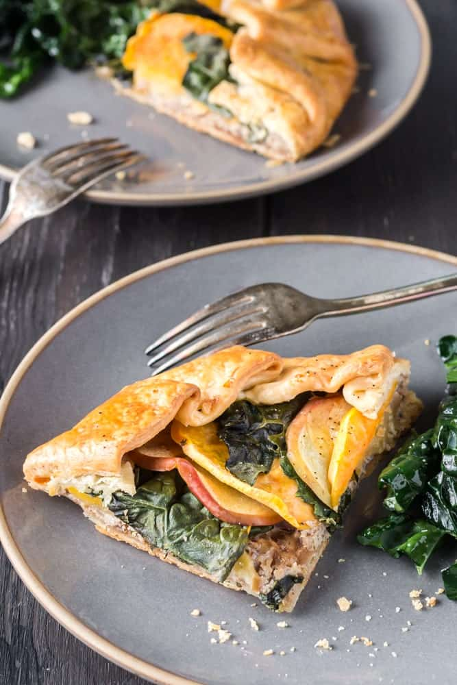 Two gray plates each with a slice of sweet potato, apple and kale galette and a small side kale salad