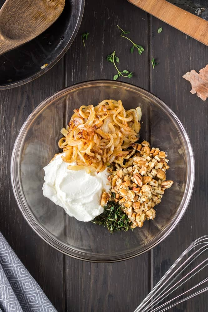 glass mixing bowl filled with white ricotta, golden caramelized onions, green chopped thyme and chopped pecans