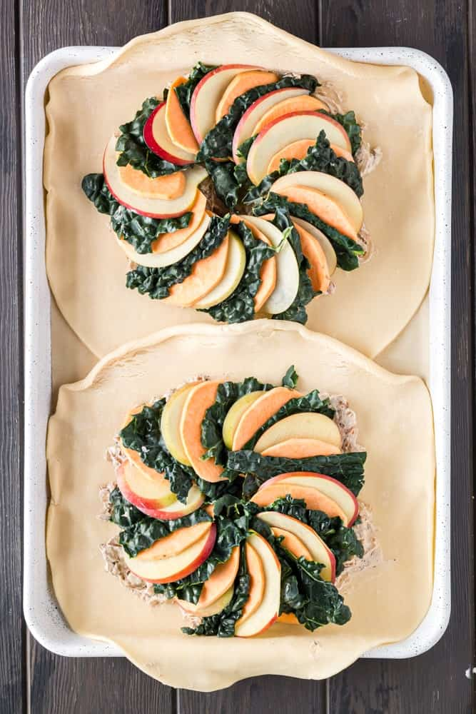 golden brown round sweet potato, apple and kale galette filled with orange slices of sweet potato, green torn kale leaves and white apple slices on a white baking sheet lined with brown parchment paper before folding edges of the pie crust over the vegetables