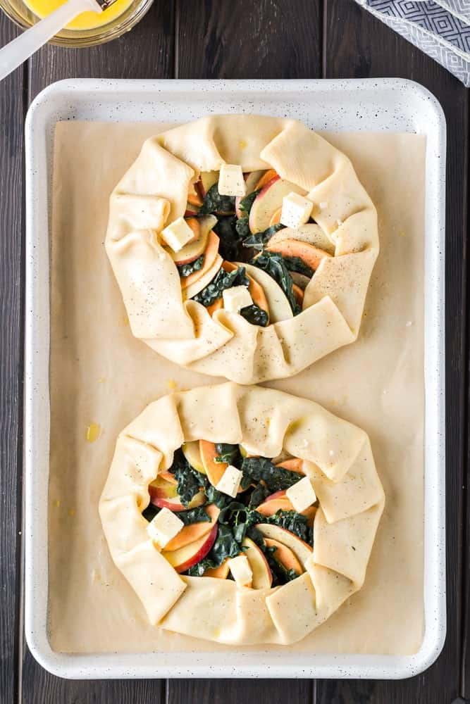 golden brown round sweet potato, apple and kale galette filled with orange slices of sweet potato, green torn kale leaves and white apple slices on a white baking sheet lined with brown parchment paper before baking